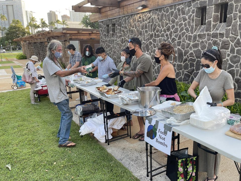 Volunteers from Food Not Bombs Honolulu provide free hot vegetarian meals free of charge to the public at Thomas Square Park on Sunday, October 10, 2021. The group provides free meals and hygenic supplies at the same location every week. (Ronen Zilberman photo Civil Beat)