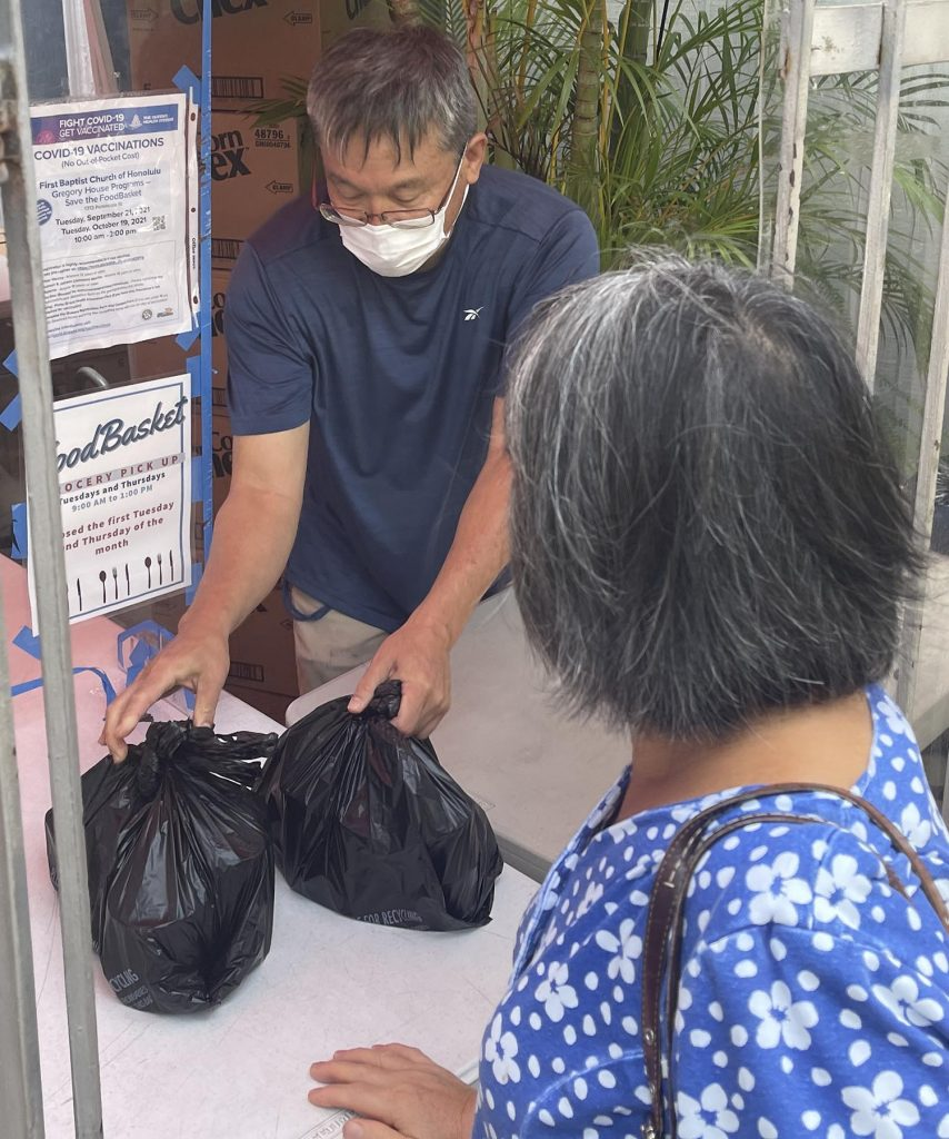 Dean Masumoto volunteers to give out food donations at the Food Basket grocery pick-up through the First Baptist Churh of Honolulu on Tuesday, October 12, 2021. (Ronen Zilberman photo Civil Beat)