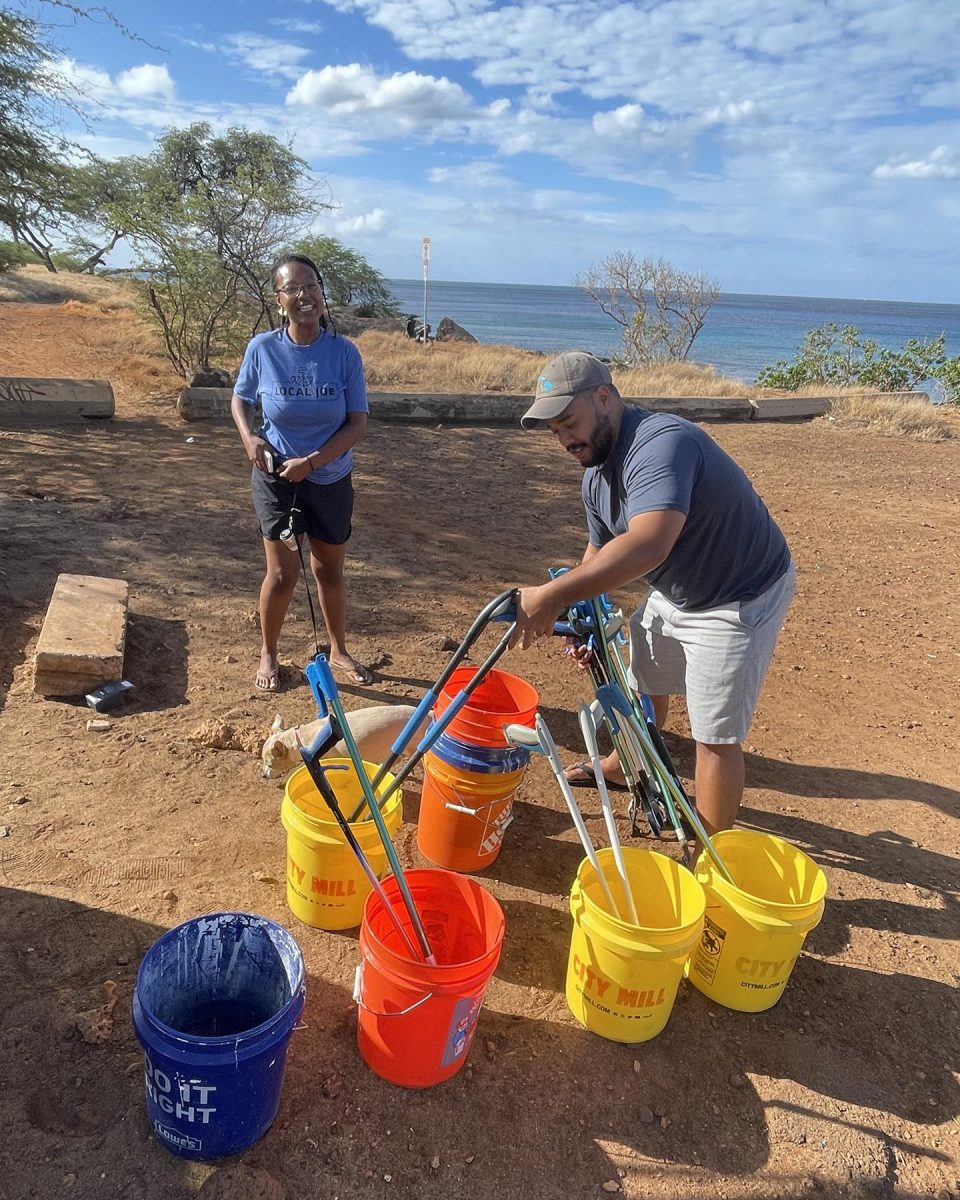 """Jessica and Jeffrey Haynes prepare supplies for collecting trash from the Kahe Point Beach Park in Kapolei Sunday, October 17, 2021. The monthly beach cleanup is done by a group of friends that get together to clean up their beloved park.  Jessica says the reason they organize the monthly beach cleanup is, """"...to encourage groups of people to empower themselves, come together, and do community service of all types."""" (Ronen Zilberman photo Civil Beat)"""